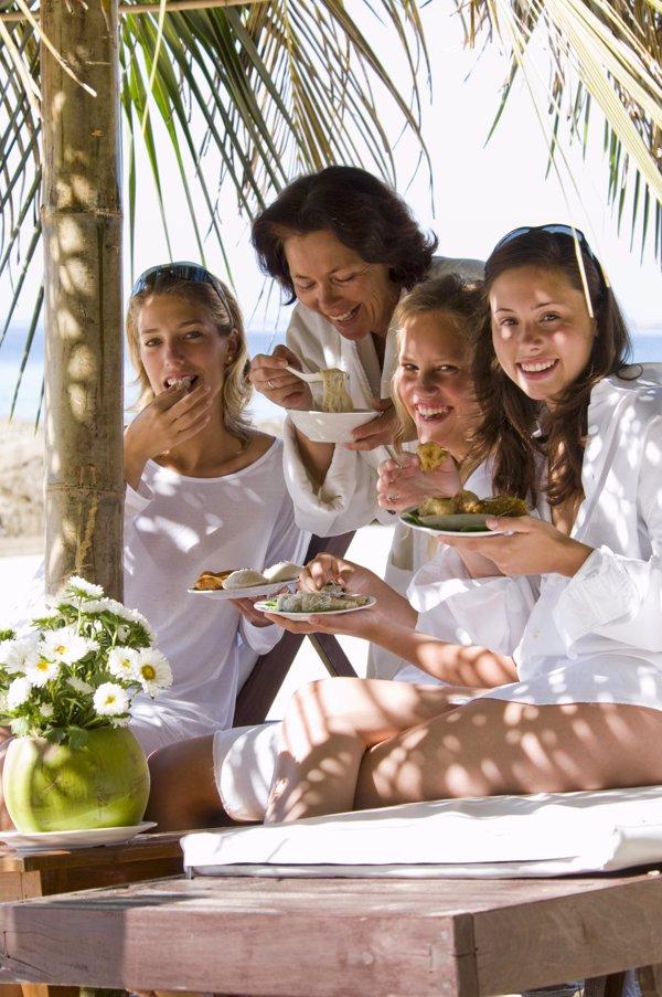 Madre con tres hijas disfrutando de ellas en la playa, escuchar la herramienta perfecta para llevarse bien con los hijos