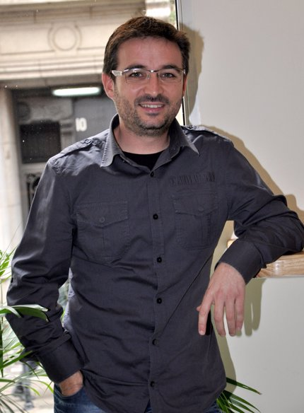 Jordi Évole posando apoyando un brazo en la pared, con camisa gris de sport, pantalón negro, y camiseta negra