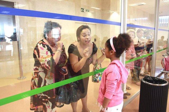 Una niña saharaui se despide de su familia de acogida en el aeropuerto de Málaga
