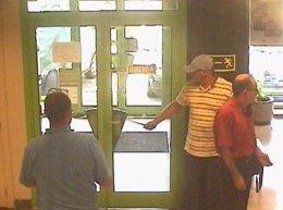 El atracador vigila la entrada de la entidad bancaria