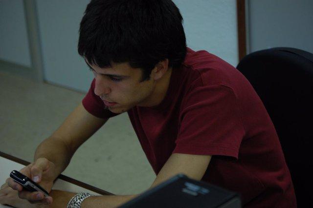 Un Joven Usa Su Teléfono Móvil Para Mandar Un SMS.