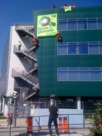 """Activistas de Greenpeace se cuelgan de la sede de BP en Madrid para cambiar su logo por otro """"teñido"""" de petróleo"""