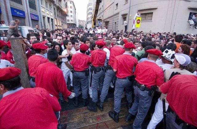 Agentes de la Policía Foral contienen al público antes de un encierro.