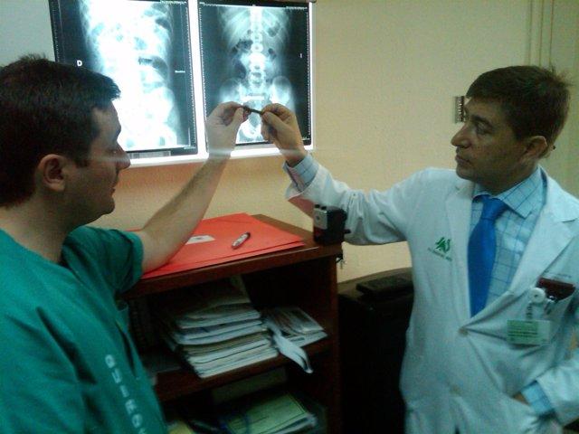 Médicos sosteniendo un iman ingerido por un niño y radiografías