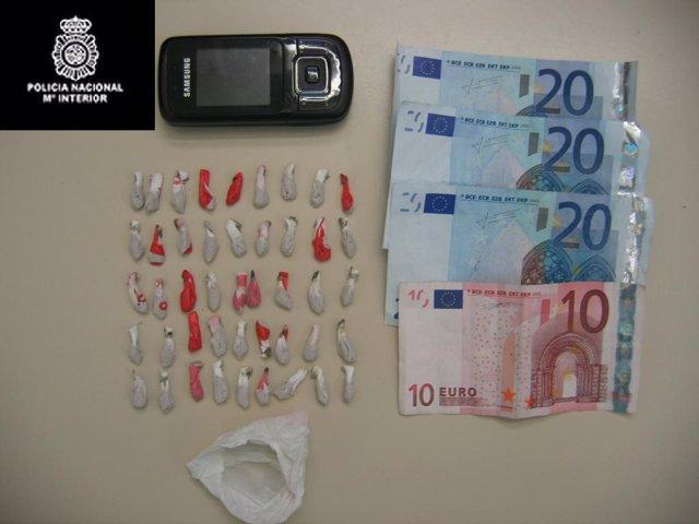 Las dosis de heroína incautadas, junto al dinero y el móvil.