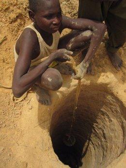 Niño extrayendo agua de un pozo