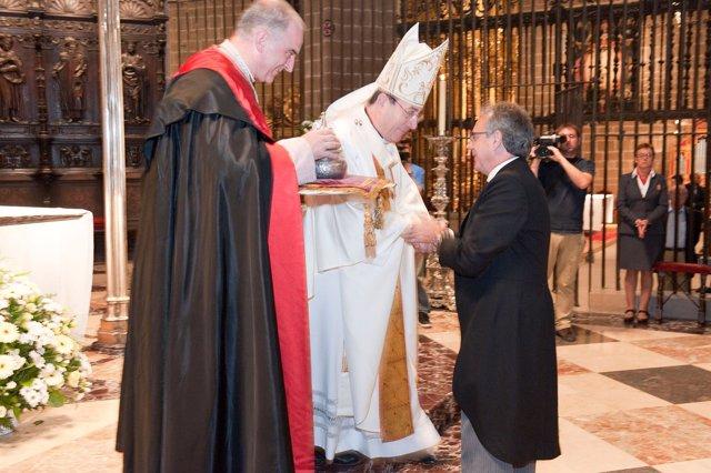 El presidente Sanz entrega la urna con el donativo al arzobispo en la ofrenda a