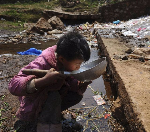 Niño pobre bebiendo agua