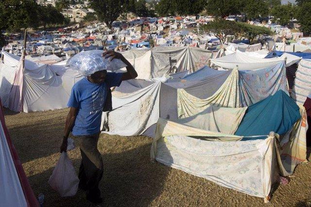 Un hombre carga con provisiones en un campamento en Haití