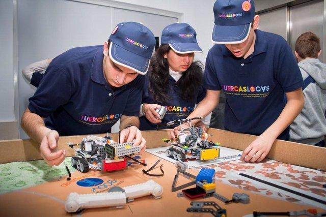 Tres integrantes del equipo de robótica trabajan en su proyecto.