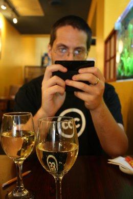 Usando un móvil smartphone durante la cena comida