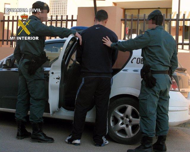 La Guardia Civil introduce en el coche patrulla al joven detenido