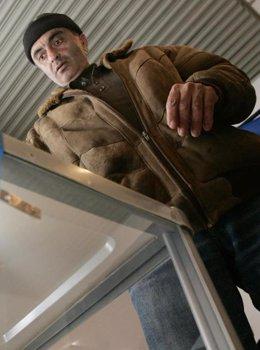 Un inmigrante deposita su voto en una urna.