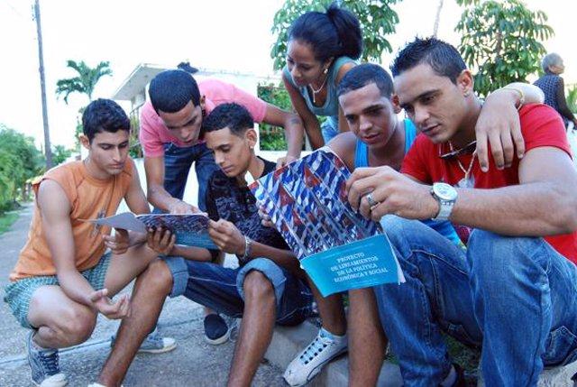 Jóvenes leyendo el proyecto sobre las reformas económicas en Cuba.