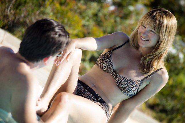 Una mujer en bikini sonríe en la piscina, verano, calor
