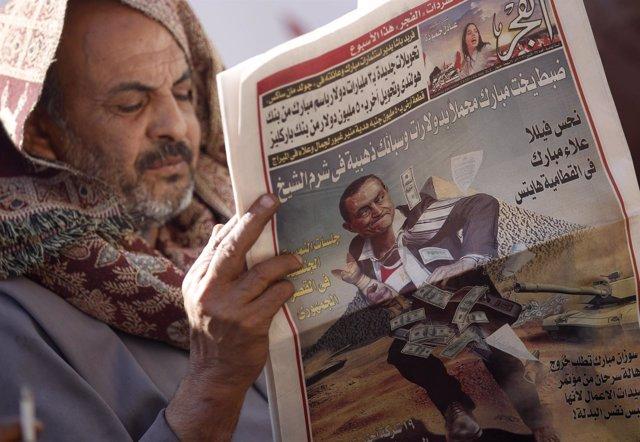 Un hombre leyendo un periódico en la Plaza Tahrir de El Cairo