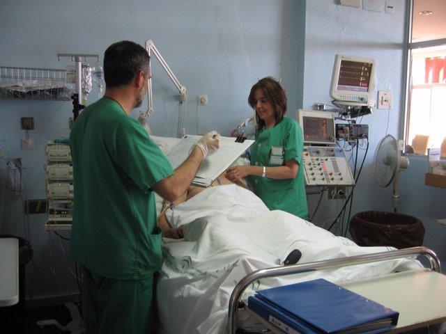 Dos Sanitarios Atienden A Un Paciente En Un Hospital