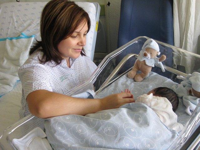 Una Madre Cuida A Su Bebé En La Cuna De Un Hospital