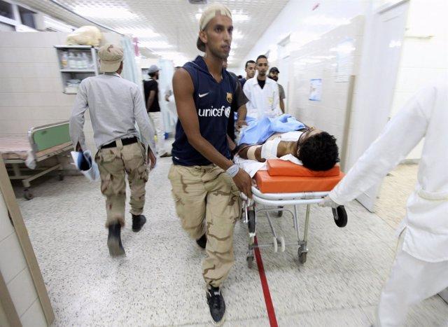 Rebeldes Libios Trasladan A Un Compañero Herido En Combate