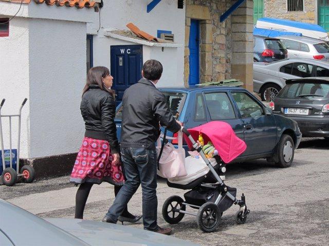 Una pareja pasea a su hijo en un carrito