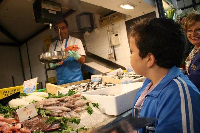 Un Escolar Visita Uno De Los Puestos De Pescadería Del Mercado De Abastos