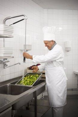 Un Cocinero Lava Alimentos En La Cocina De Un Restaurante