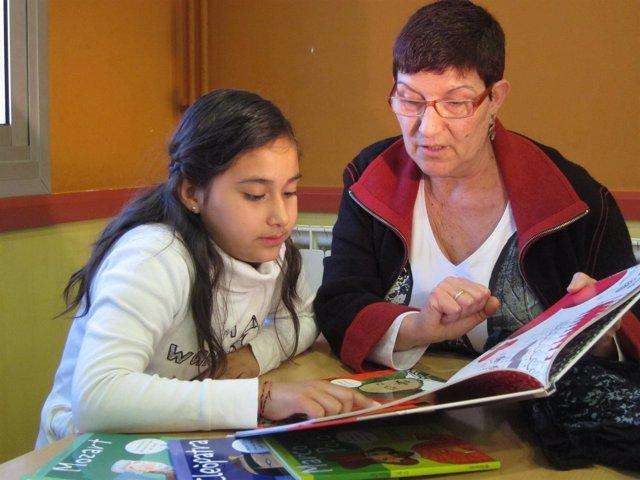 Voluntaria Ayuda A Leer A Una Niña