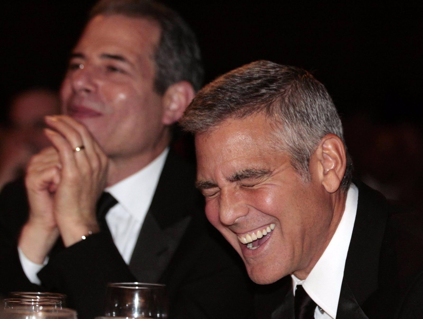 El actor George Clooney riéndose a carcajadas en una cena