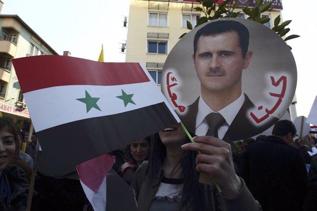 Recurso De Una Manifestación Siria Con La Bandera Y La Cara De Al Assad
