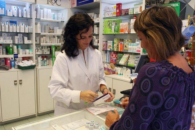 Una farmacéutica atiende en su botica a una usuaria