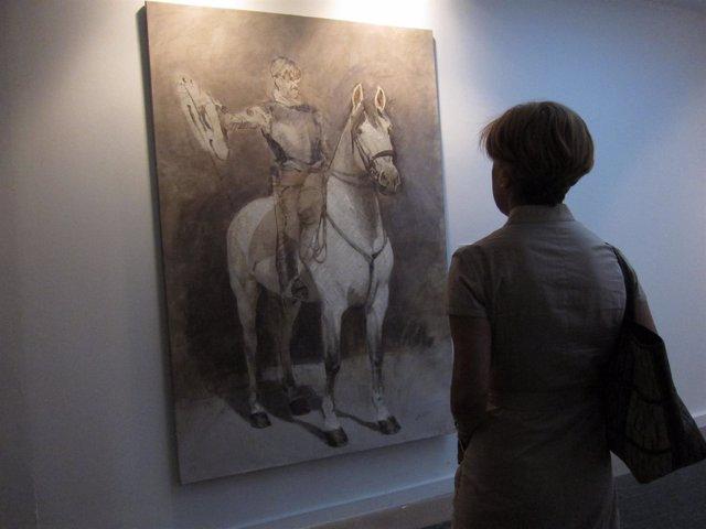Una mujer mira una obra de Ángel Luis Iglesias expuesta en La Salina.