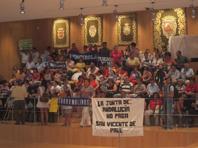 Miembros de ONG afectadas por el impago, durante el pleno