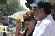 Un matrimonio se protege del sol con abanico y gorra