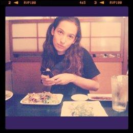 Chica usando el móvil o smartphone en un restaurante durante la cena
