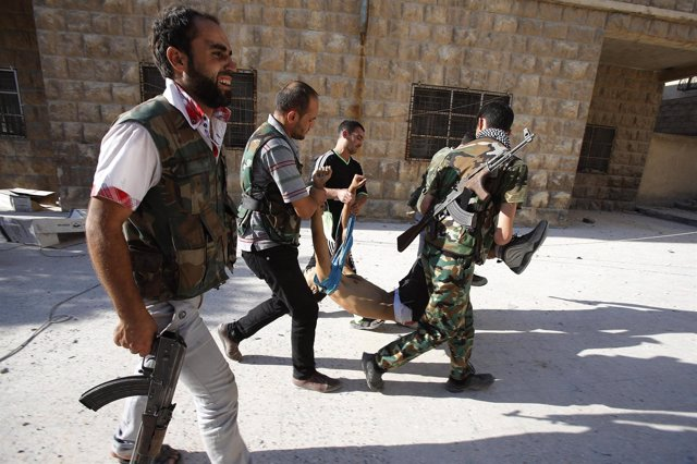 Rebeldes sirios trasladan el cuerpo sin vida de un compañero