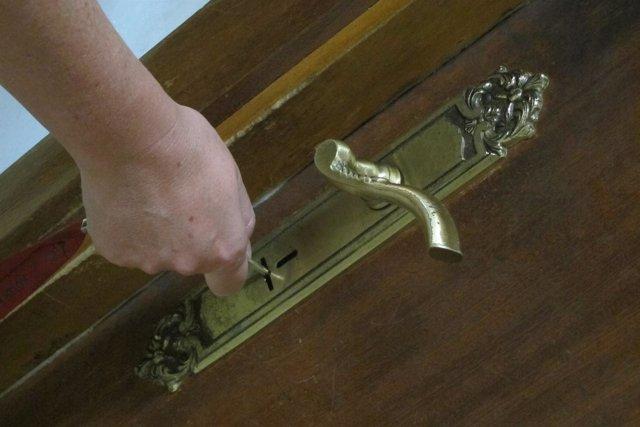 Una mujer abre la puerta de su vivienda