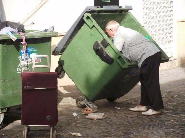 Un mendigo busca comida en un contenedor