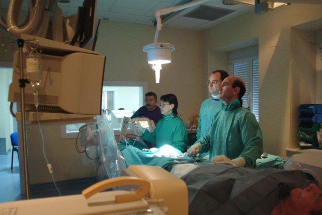 Médicos cirujanos observan las constantes vitales de un paciente