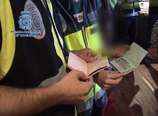 Policías inspeccionando pasaportes falsos