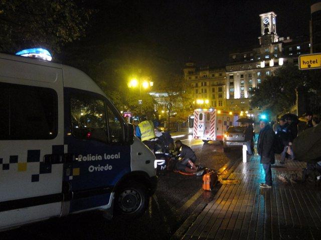 Personal sanitario atiende a la mujer herida en el lugar del accidente.