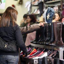 Consumidor comprando botas en una tienda