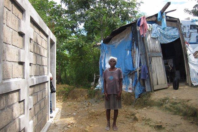 Anciana Al Lado De Su Choza Y De Su Nueva Casa En Haití