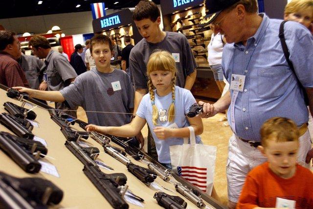 Gente comprando armas en una feria de la Asociación Nacional del Rifle en EEUU
