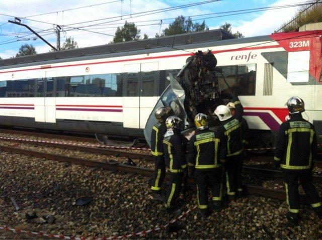 Bomberos retirando coche de la vía del tren