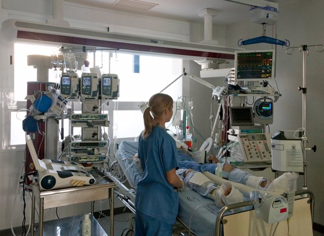 Enfermera atiende a paciente encamado en UCI