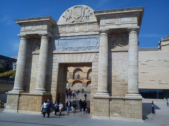 Turistas pasando bajo la Puerta del Puente, en el casco histórico
