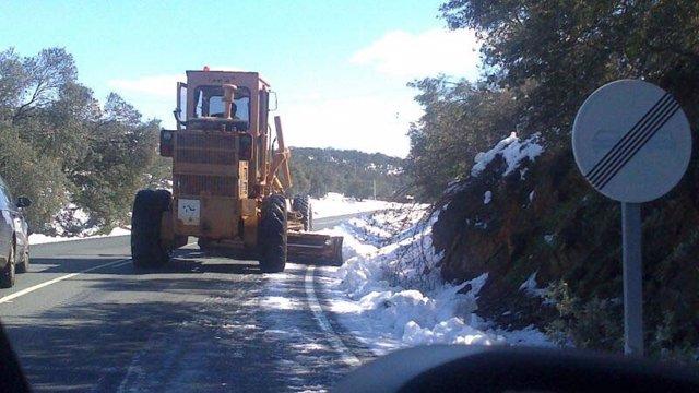 Una máquina quitanieves despeja una carretera.