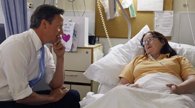 David Cameron habla con una paciente de un hospital