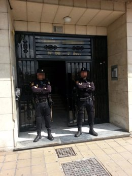 Agentes custodiando puerta vivienda