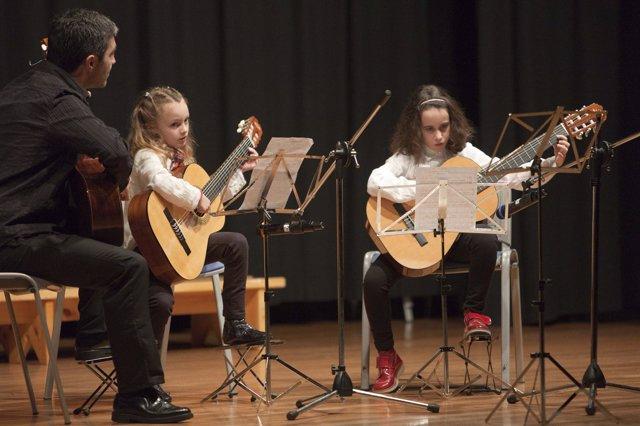Niños tocando la guitarra en la escuela de música de Camargo
